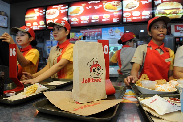 Philippines' leading fast-food giant Jollibee Foods employees attend to customer orders at a Jollibee store in Manila on October 14, 2015. Jollibee Foods announced on October 13 it had acquired 40 percent of an upmarket US hamburger chain for 99 million USD.      AFP PHOTO / Jay DIRECTO        (Photo credit should read JAY DIRECTO/AFP/Getty Images)